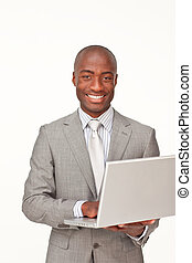 Afro-American businessman using a laptop and smiling at the ...