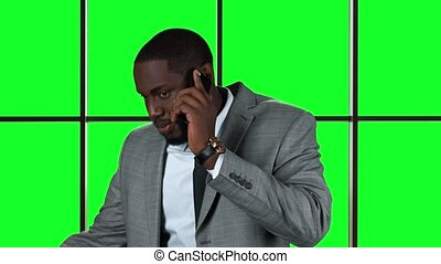 Afro-american businessman with cellphone. Man on chromakey...