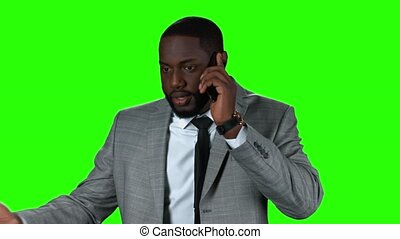 Afro-american businessman with phone. Smiling man on green...