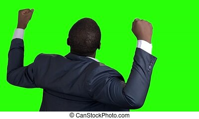 Afro american businessman with raised fists, back view.