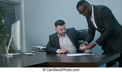 Afro-american businessmen counting money on desk and giving bills to his caucasian partner, they shaking hands positively