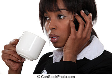 Afro-American businesswoman drinking coffee and talking on her cell