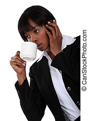Afro-American businesswoman talking on her cell and drinking coffee