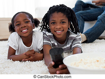 Afro american children watching television and eating pop...