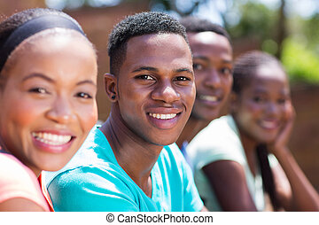 afro american college boy sitting with friends