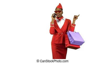 Afro american comes with shopping bags talking on the phone, she's a flight attendant. Alpha channel