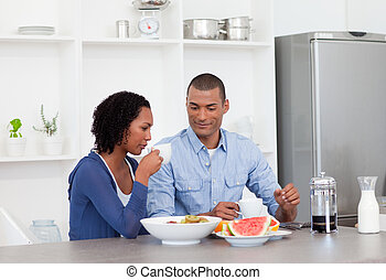 Afro-american couple having breakfast in the kitchen