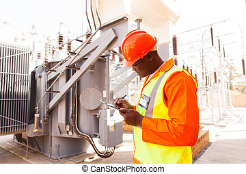 afro american electrical engineer writing on clipboard
