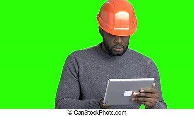 Afro american engineer working on digital tablet. Handsome...