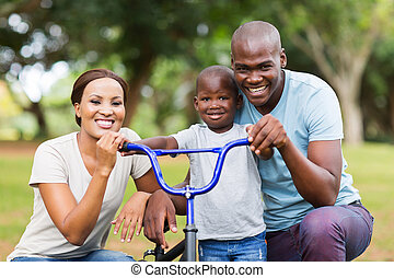 afro american family having fun together outdoors - adorable...