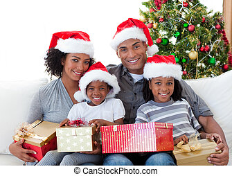 Afro-American family holding Christmas presents at home