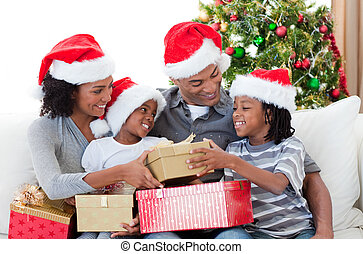 Afro-American family holding Christmas gifts