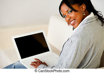 Afro-american female browse the Internet on laptop -...