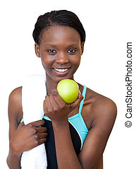 Afro-american fitness woman eating an apple against a white...