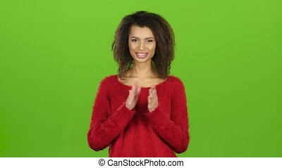 Afro american girl clapping her hands and smiles, green screen
