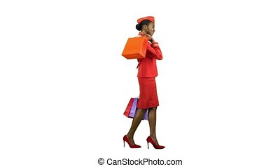 Afro american girl in a red suit comes with shopping bags she's a flight attendant. Alpha channel. Side view