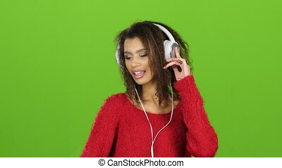Afro american girl dancing with headphones on green screen, close-up