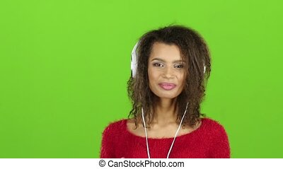 Afro american girl dancing with headphones, green screen. Slow motion