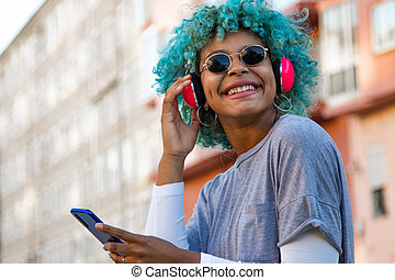afro american girl smiling with headphones and mobile phone in the city