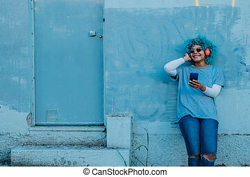 afro american girl with mobile phone and headphones on the street