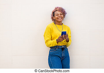 afro american girl with smartphone on the street wall