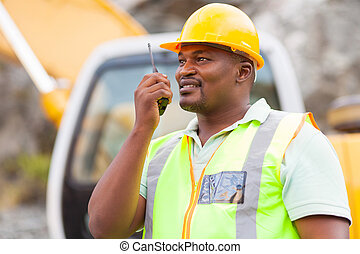 afro american industrial worker talking on walkie-talkie
