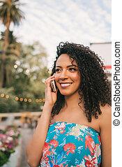 Afro American latin woman talking on the phone.