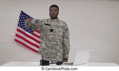 Afro-american male soldier in camouflage sitting in office -...