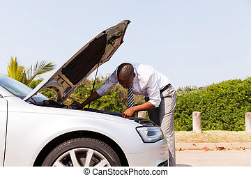 afro american man looking at broken down car engine by side...