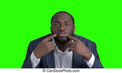 Afro american man making grimace on green screen. Dark...