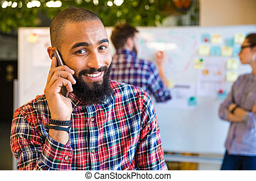 Afro american man talking on the phone in office