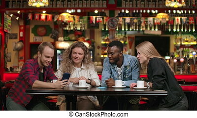 Afro-American man with friends in a cafe laughs and spends...