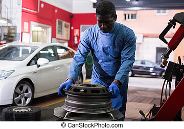 Afro american man working with tire fitting machine at auto car repair service center