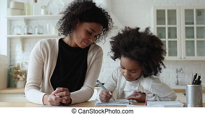 Afro american young mom, babysitter or tutor helping cute school child daughter checking homework writing sitting at kitchen table. Mixed race parent teaching kid girl learning education at home.