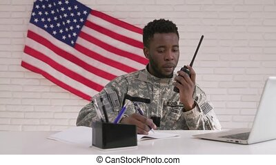 Afro-american officer using radio transmitter in his office