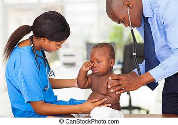afro american pediatrician and nurse examining a baby boy -...