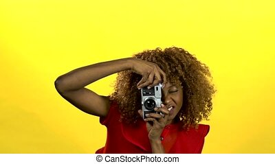 Afro american photographer holds a camera in her hands and...