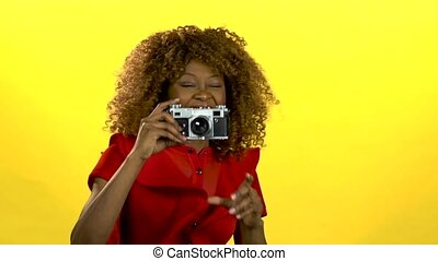 Afro american photographer holds a camera in her hands ....