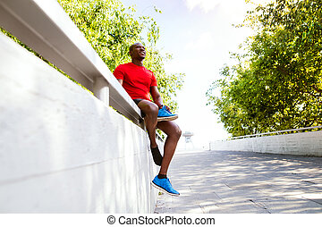 Afro-american runner in the city sitting on concrete wall restin