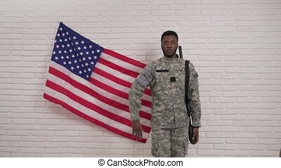 Afro-american soldier saluting in front of American flag -...