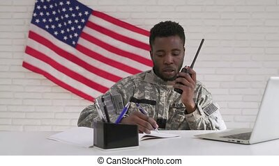 Afro-american soldier using computer and portable radio set...