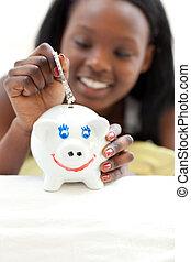 Afro-american teen girl putting money in a piggy-bank