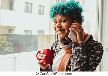 afro american woman at home window with mobile phone and cup