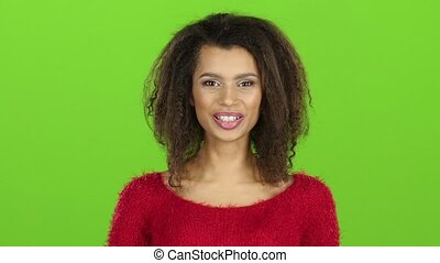 Afro american woman contagiously laughs on green screen. Slow motion