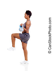 afro american woman doing exercise with kettle bell