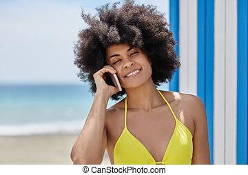 Afro american woman in yellow bikini talking on mobile