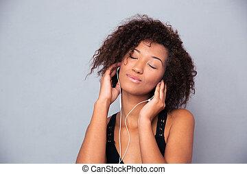 Afro american woman listening music in headphones