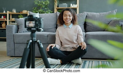 Afro-American woman vlogger talking and gesturing recording video with camera at home.