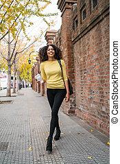 Afro-american woman walking on the street.