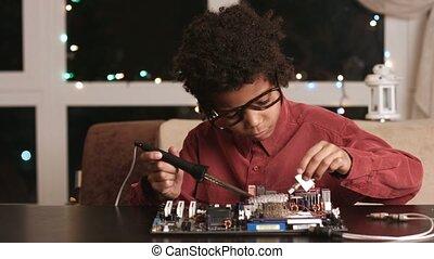 Darkskinned boy solders motherboard.